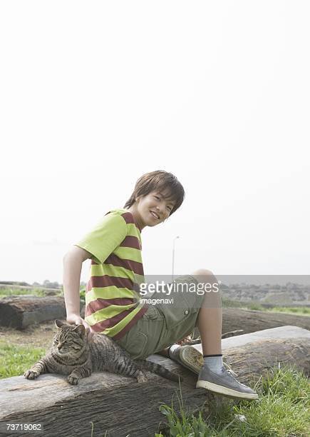 smiling boy with cat sitting on the lying tree in the field - 14歳から15歳 ストックフォトと画像