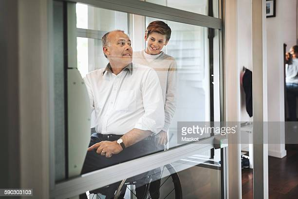 Smiling boy with father in wheelchair lift at home