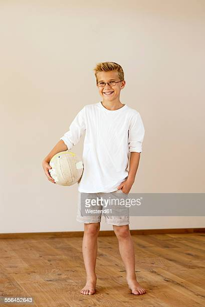 Smiling boy with football at home