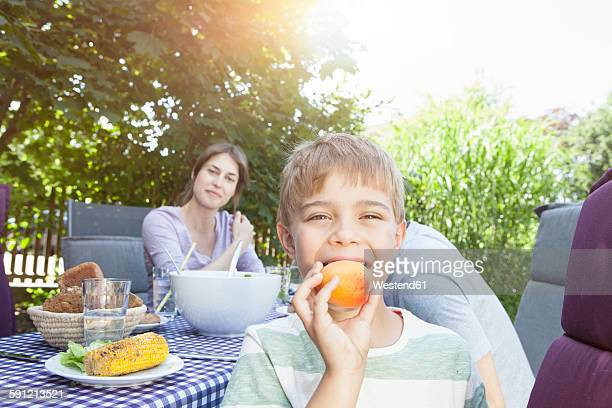 Smiling boy with his family holding a fruit at garden table