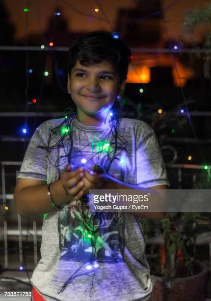 Smiling Boy With Illuminated String Light Standing In Balcony At Night