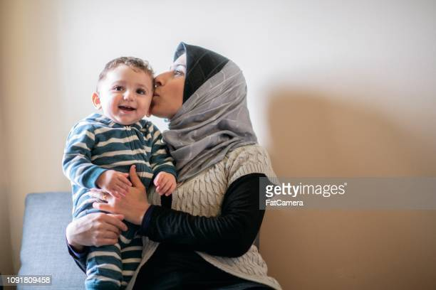 Smiling boy with mom kissing him