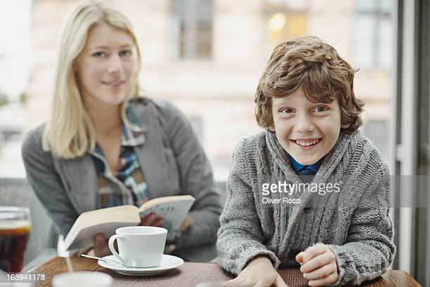 Smiling boy with mother in a café