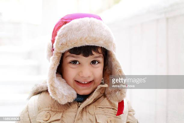 Smiling boy with red aviator fur hat