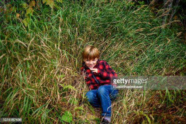 smiling boy with stitches on his face sitting in long grass, lake superior provincial park, united states - lake superior provincial park stock pictures, royalty-free photos & images