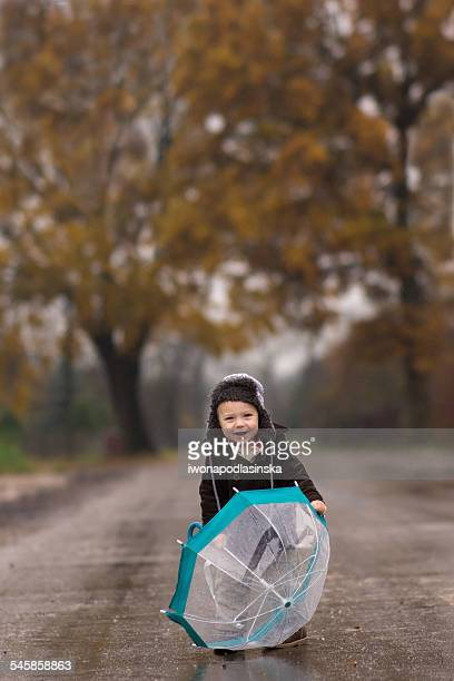 Smiling boy with umbrella on country road