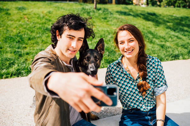 Smiling boyfriend taking selfie with dog and girlfriend through smart phone on footpath