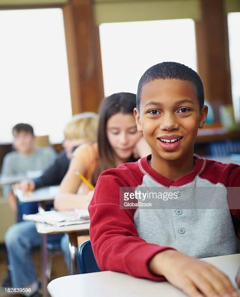Lächelnde Mädchen und Jungen sitzen in einer Reihe