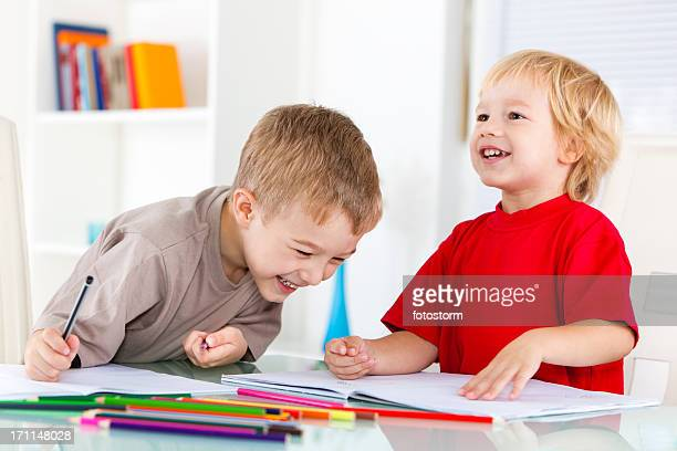 Smiling boys drawing