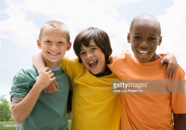 smiling boys hugging outdoors - multiculturalismo foto e immagini stock