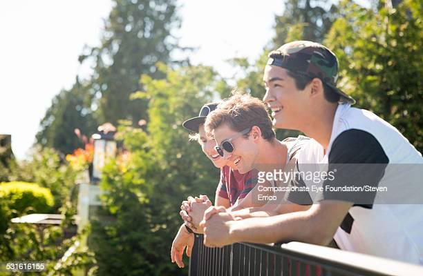 Smiling boys leaning on balcony