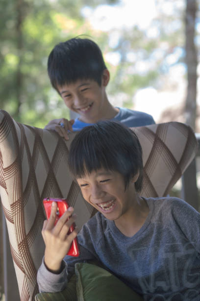 Smiling Boys Looking At Mobile Phone
