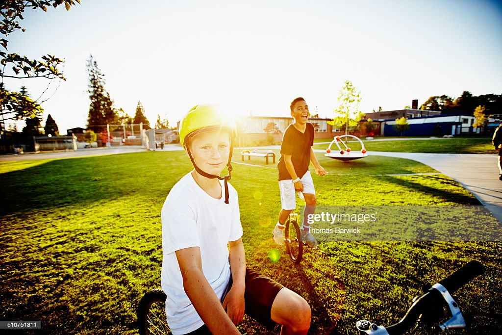 Smiling boys on bicycle and unicycle on field : Stock Photo
