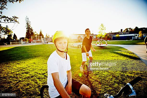 Smiling boys on bicycle and unicycle on field