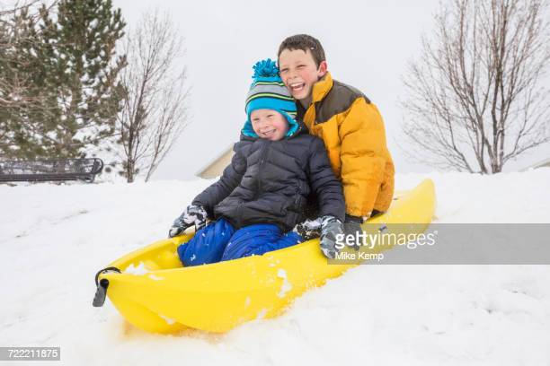 smiling boys sliding on toboggan on hill in winter - yellow coat stock pictures, royalty-free photos & images