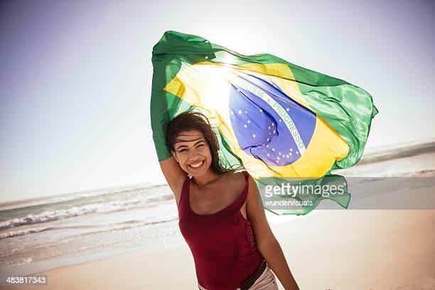 Sorridente Menina com Bandeira Brasileira na praia