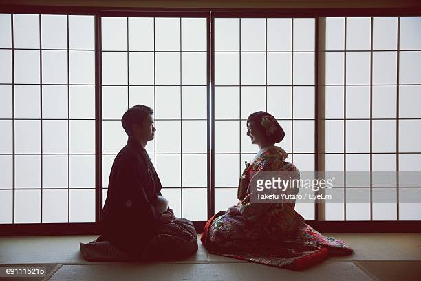 Smiling Bride And Groom Sitting Face To Face Against Window During Wedding