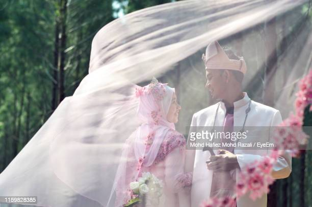 smiling bride and groom standing in forest seen through scarf - ベール ストックフォトと画像