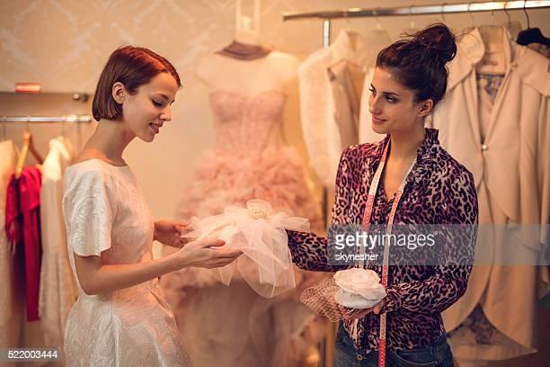 Smiling bride choosing wedding hat in clothing store.