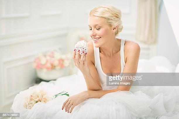 Smiling bride eating cupcake on bed