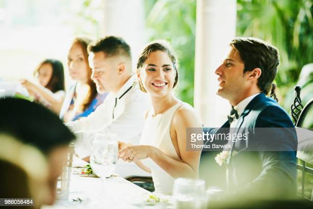 Smiling bride sitting with groom during outdoor wedding reception dinner