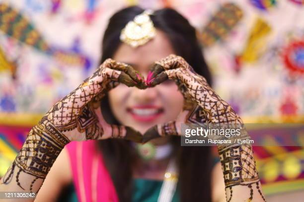 smiling bride with henna tattoo making heart shape - tattoo designs hearts stock pictures, royalty-free photos & images