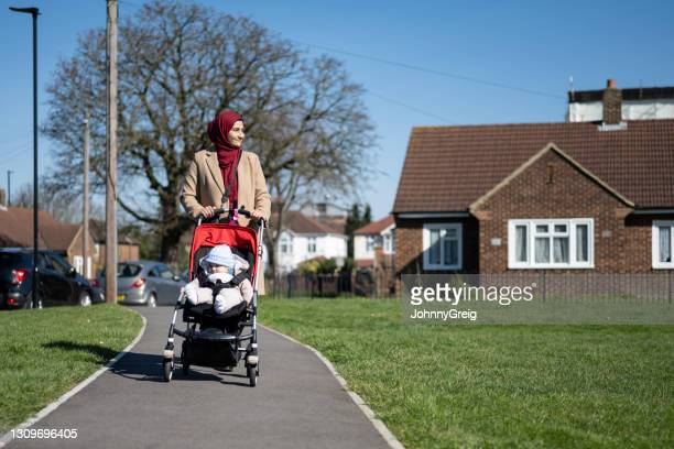 smiling british asian mother walking with baby in stroller - religious dress stock pictures, royalty-free photos & images
