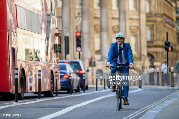 smiling british businessman in early 30s cycling to work - bicycle stock pictures, royalty-free photos & images