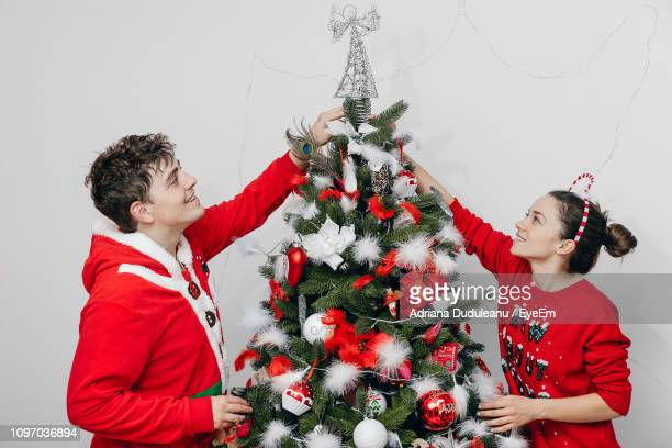 Smiling Brother And Sister Decorating Christmas Tree