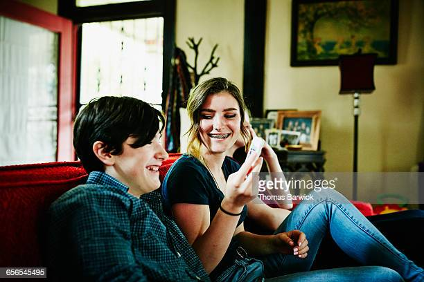 Smiling brother and sister looking at smartphone