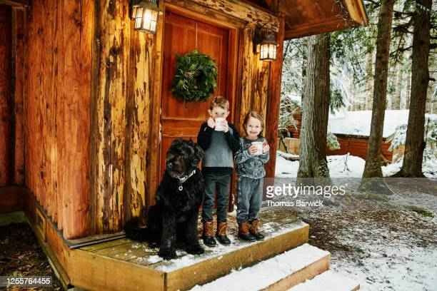 smiling brother and sister standing on front porch of winter cabin with dog while drinking hot chocolate - one animal stock pictures, royalty-free photos & images