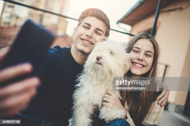 Smiling Brother and Sister Taking Selfie with Their Dog