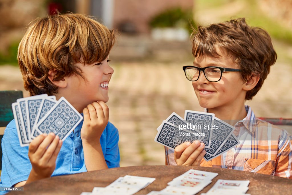 Smiling brothers playing cards at table in yard : Stock Photo