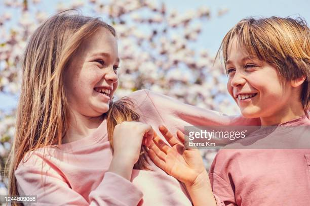 smiling brunette boy and girl standing outdoors, teasing each other. - richmond upon thames stock pictures, royalty-free photos & images