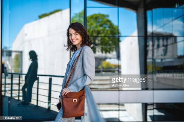 smiling brunette businesswoman taking classes on campus - shoulder bag stock pictures, royalty-free photos & images