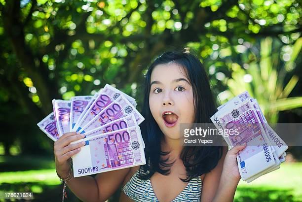 A smiling brunette girl holding euro