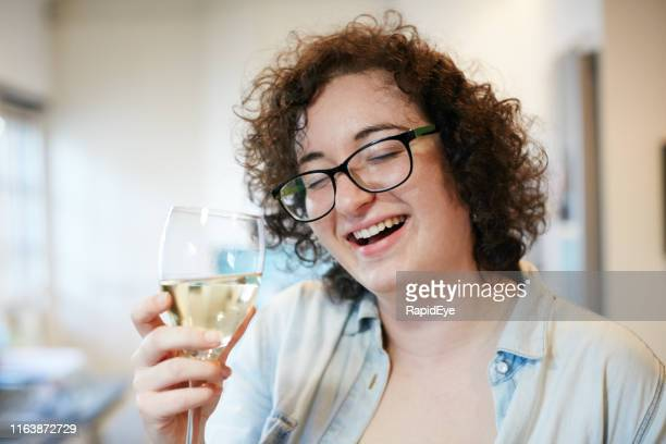 smiling brunette in eyeglasses looks at glass of wine - drunk woman stock pictures, royalty-free photos & images
