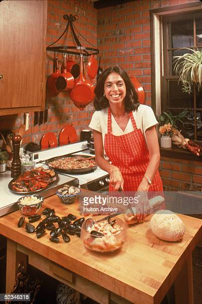 A smiling brunette woman cuts bread next to mussells on a chopping block in a kitchen as a large pan simmers on the stove 1970s