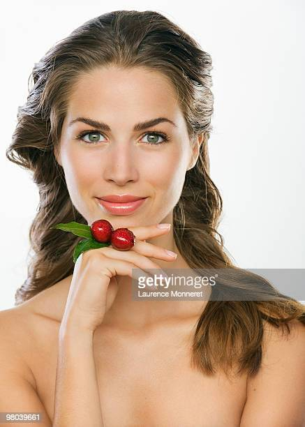 Smiling brunette woman holding cherries as a ring
