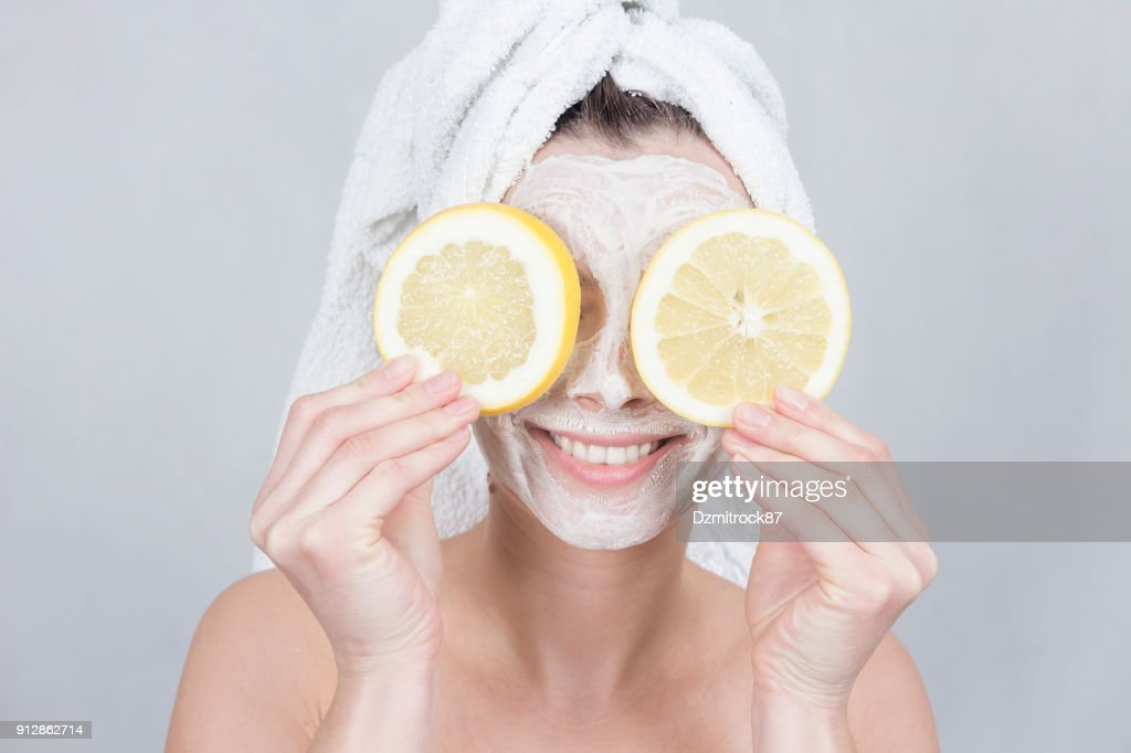Smiling brunette woman holding two slice of lemon in front of her face. woman with moisturizing facial mask. Beauty and skin care concept. : Stock Photo