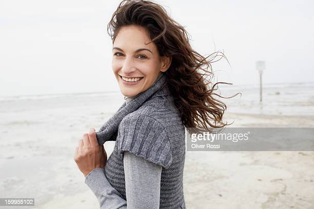 Smiling brunette woman on the beach, portrait
