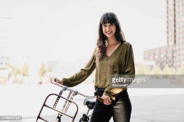 smiling brunette woman with dutch roadster - blouse stock-fotos und bilder