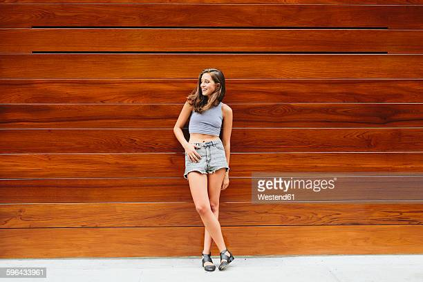 Smiling brunette young woman leaning against wooden wall