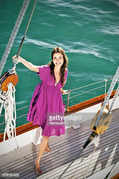 smiling brunette young woman on a sailing ship - purple dress stock pictures, royalty-free photos & images