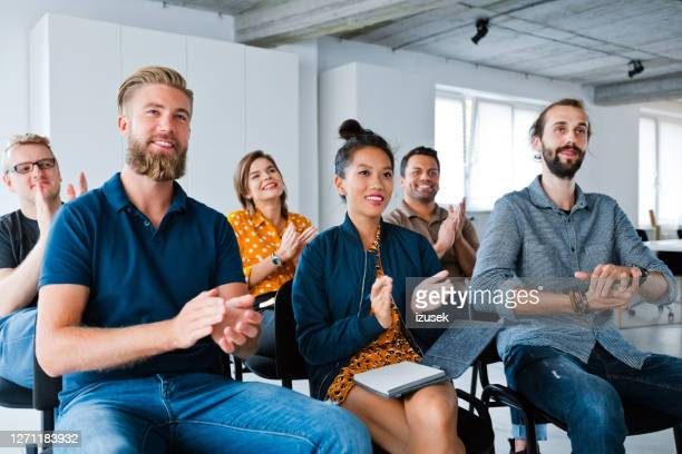 smiling business colleagues clapping at workplace - clapping hands stock pictures, royalty-free photos & images