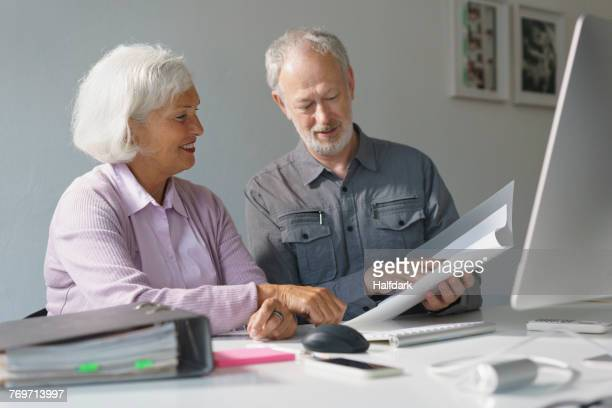 Smiling business colleagues discussing over documents at desk in office
