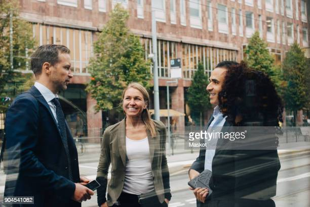 smiling business colleagues discussing while standing on street seen from glass - mid adult women stock pictures, royalty-free photos & images