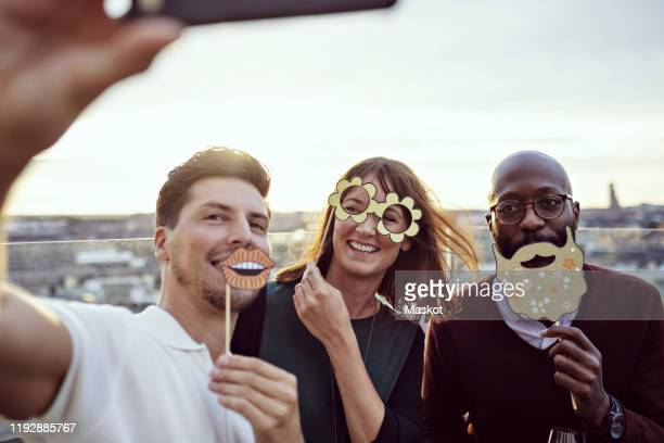 smiling business colleagues enjoying with props while taking selfie at party on terrace - 小道具 ストックフォトと画像