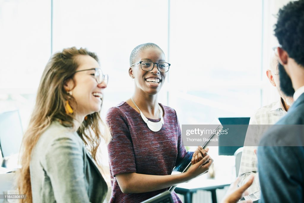 Smiling business colleagues in discussion during informal meeting in start up office : Stock Photo