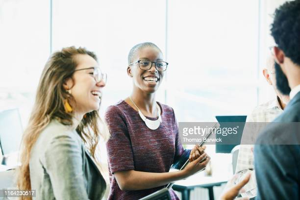 smiling business colleagues in discussion during informal meeting in start up office - diversity stock pictures, royalty-free photos & images